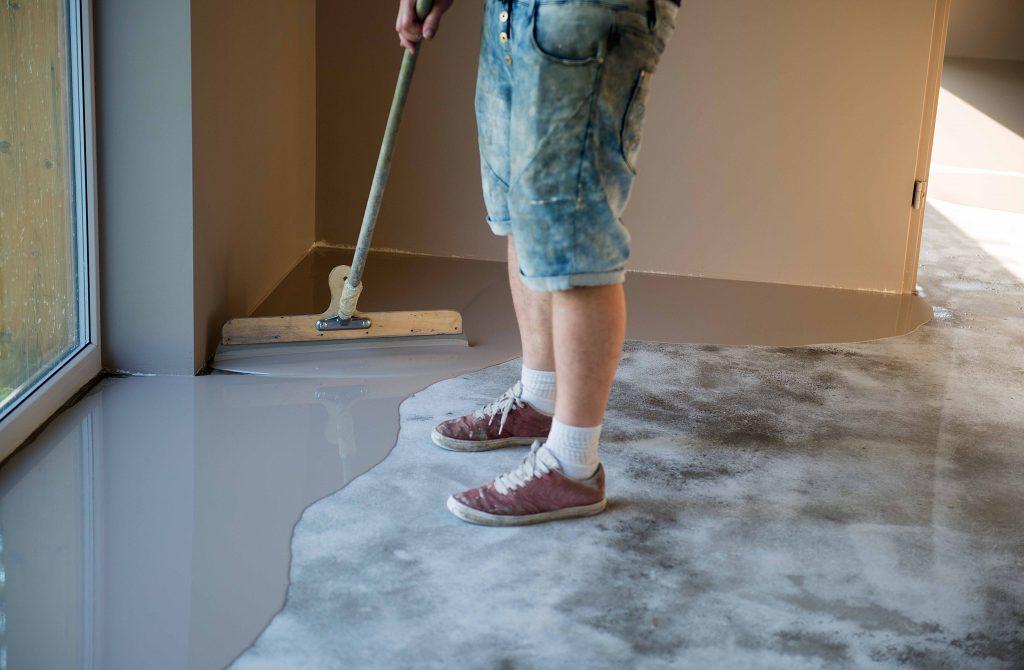epoxy-worker-pours-epoxy-resin-flooring